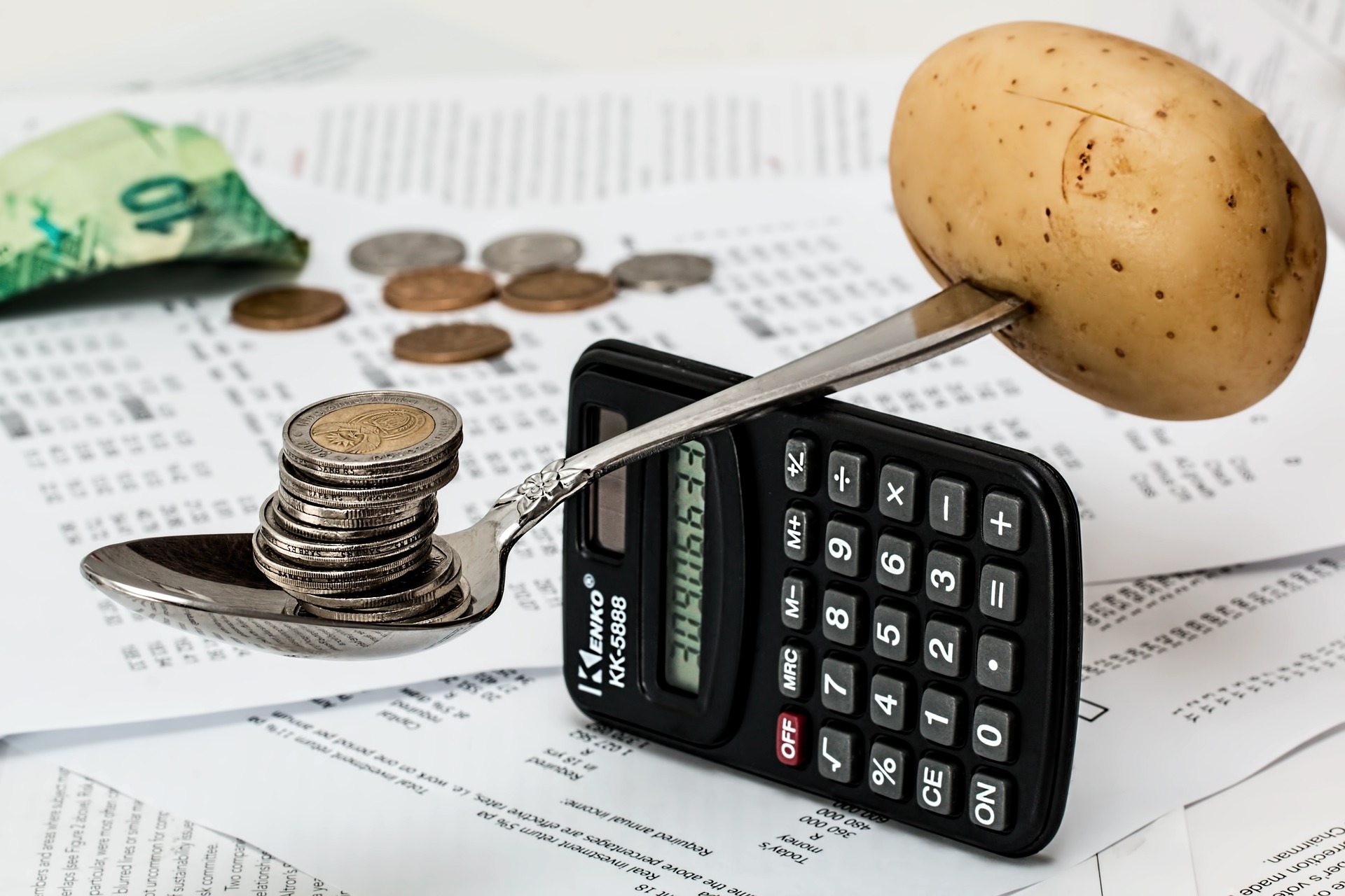Coins and potatoes balanced on a spoon and calculator