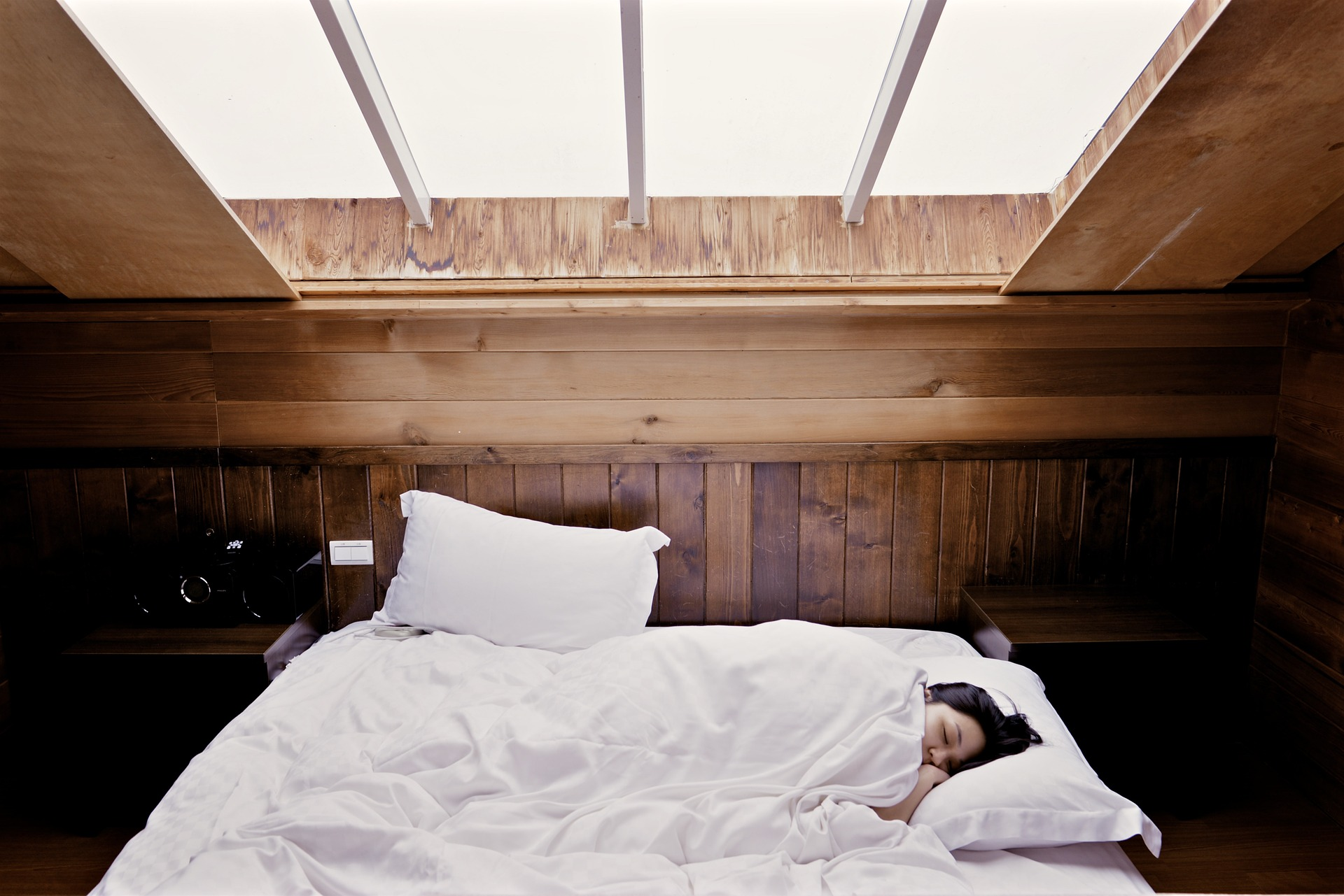Woman asleep with vaulted skylight in her living quarters