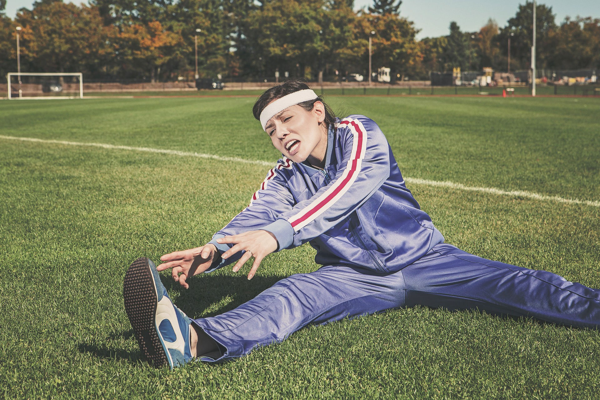 Woman stretching in trackpants on a soccer field