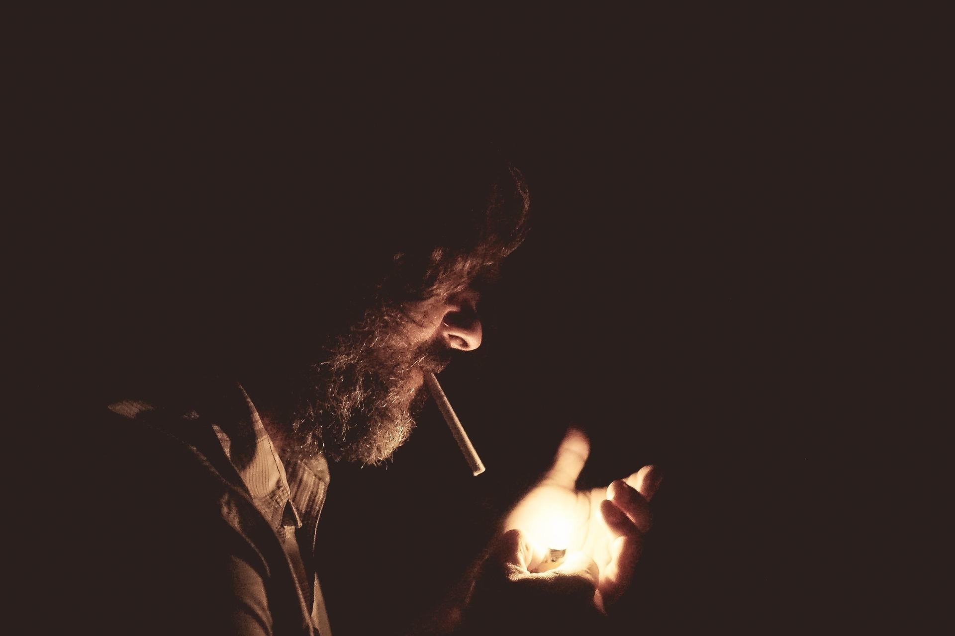 A man smokes cigarettes in the dark.